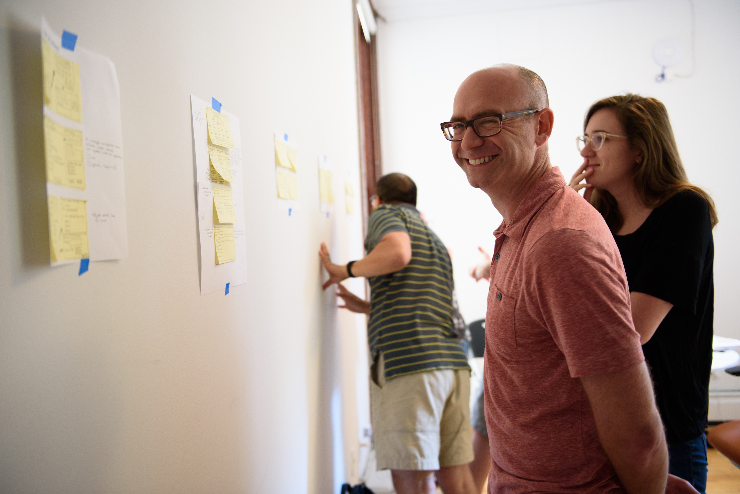 GV sprint participants stand in front of a wall with sticky notes, smiling.