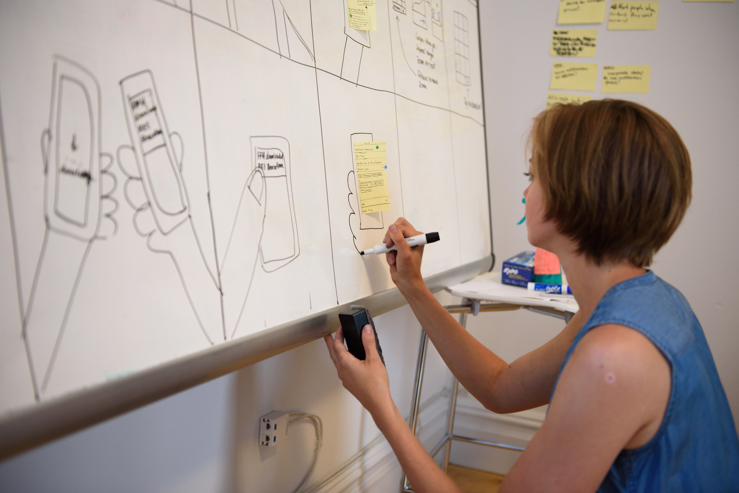 Kim Burgas drawing a hand on a whiteboard. The whiteboard is covered in storyboard illustrations and a sticky note.